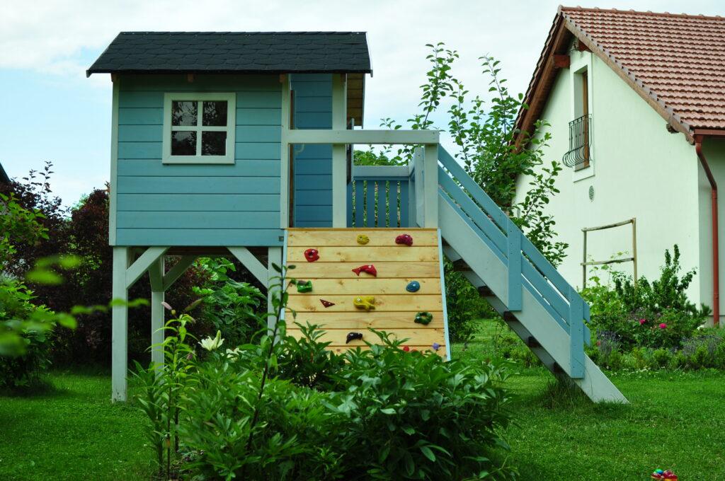 Drewniany domek ze ścianką wspinaczkową
